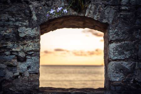 Scenic sunset over sea through window of old ruins with dramatic sky and perspective view with effect of light at the end of tunnel as travel background