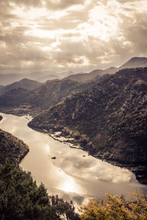 Mountains landscape in orange toned colors  around Rijeka Crnojevica river curve from high view in overcast day with dramatic sky in Europe country Montenegro