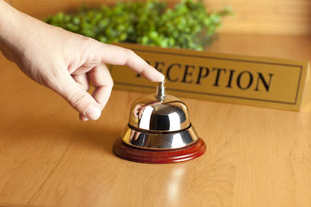 reception counter: Hand of a man using a hotel bell  Stock Photo