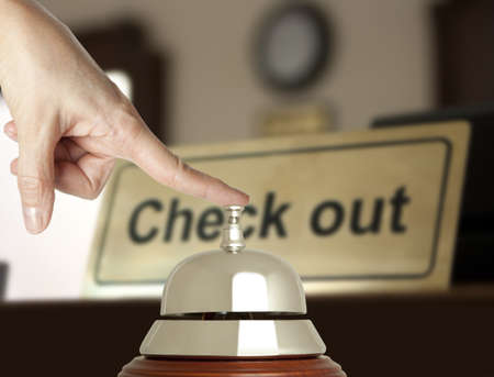 checkout button: Hand of a woman using a hotel bell  Stock Photo