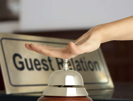 Hand of a woman using a hotel bell  photo