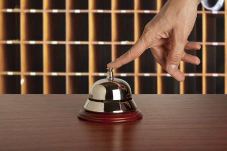 call bell: Hand of a woman using a hotel bell
