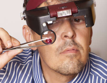 inspecting: Male jeweler looking through a magnifier to check for flaws in a ruby   Focus on ruby