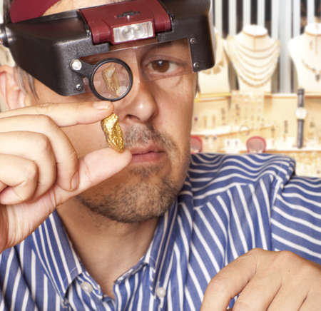 raw gold: A man holding a gold nugget jewelry