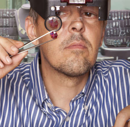 Male jeweler looking through a magnifier to check for flaws in a ruby  Focus on ruby