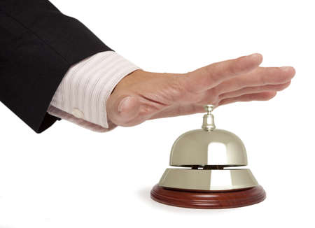 Hand van een zakenman met behulp van een hotel bell geïsoleerde