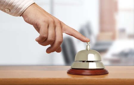 bellman: Hand of a man using a hotel bell  Stock Photo