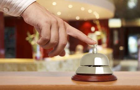recepcion: Mano de un hombre que usa una campana del hotel Foto de archivo