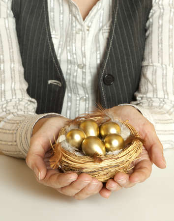 Hands holding nest with golden eggs  photo