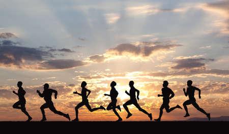 razas de personas: Marathon, siluetas negras de corredores en la puesta del sol Foto de archivo