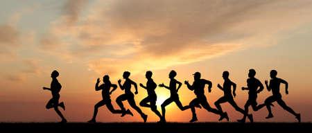 maraton: Marathon, siluetas negras de corredores en la puesta del sol Foto de archivo