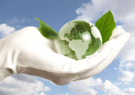 sea pollution: Globe in human hand against blue sky  Stock Photo