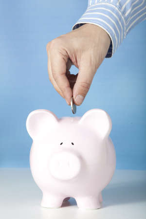 savings and loan crisis: Male hand putting coin into a piggy bank