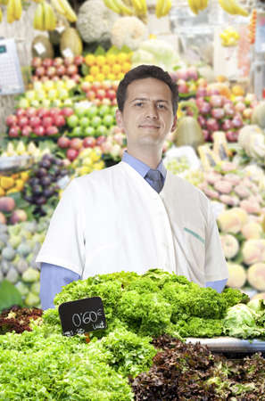 A young merchant of fruits and vegetables at the market sells lettuce Stock Photo - 15484366
