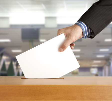 poll: Hand putting a voting ballot in a slot of box