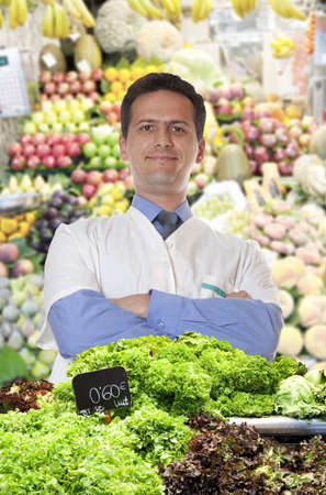 A young merchant of fruits and vegetables at the market sells lettuce photo