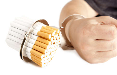 Cigarette and handcuffs isolated on white  photo