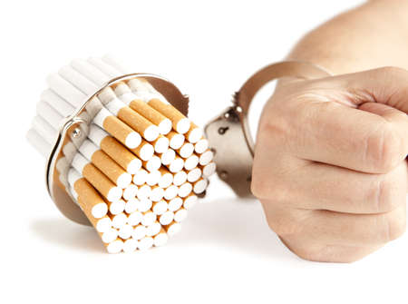 cigarette smoke: Cigarette and handcuffs isolateed on white  Stock Photo
