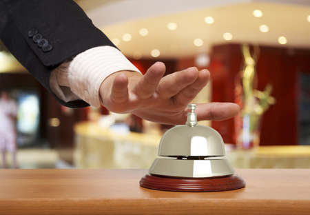 to chime: Hand of a businessman using a hotel bell