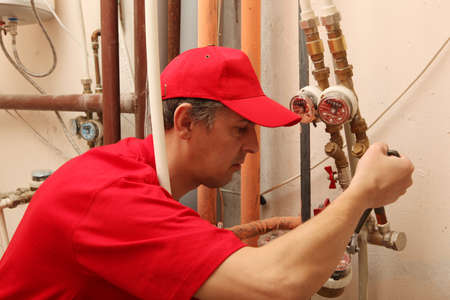 View of a plumber repairing a faucet  photo