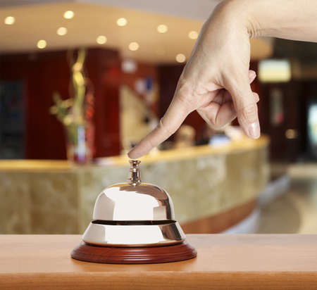 hospitality industry: Hand of a woman using a hotel bell  Stock Photo