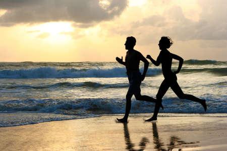 sudando: La mujer y el hombre en ejecuci�n durante la puesta del sol Foto de archivo