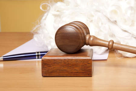 arbitrate: Gavel, judges wig and pen on the table