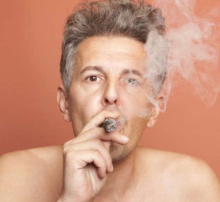 smoking a cigar: Man smoking a Cuban cigar