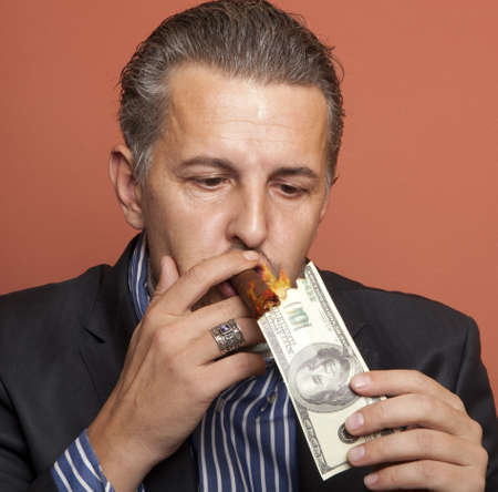 arrogant: Man lighting his cigar with 100 dollars banknote