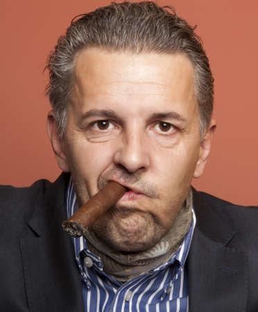 hustler: Man wearing suit gangster style smoking cigar  Stock Photo