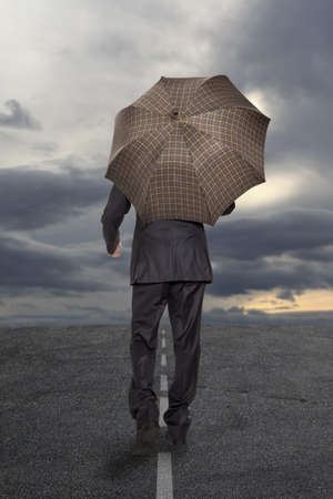 loss leader: Businessman with umbrella under a stormy sky