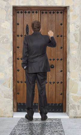 Businessman knocking at a wooden door  photo