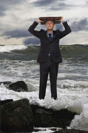 business survival: Businessman using a briefcase as shelter with stormy sky in the background  Stock Photo