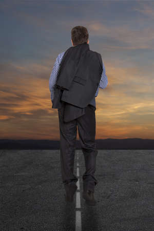 Lonely businessman is on the road against the background of stormy skies  photo
