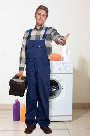 Portrait of an happy plumber against the washing machine photo