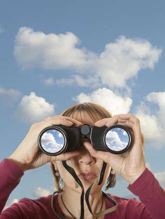 conclusion: Mujer atractiva con los prismáticos en el cielo