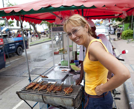 street food: A woman buys traditional Thai food from street cooks Stock Photo