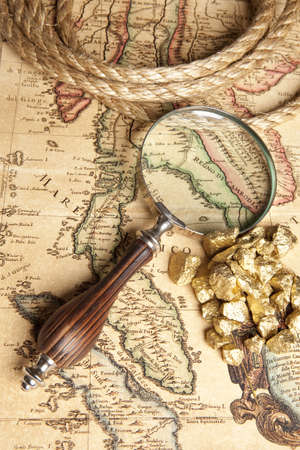 Magnifying glass, ancient old map and Gold Nugget  photo
