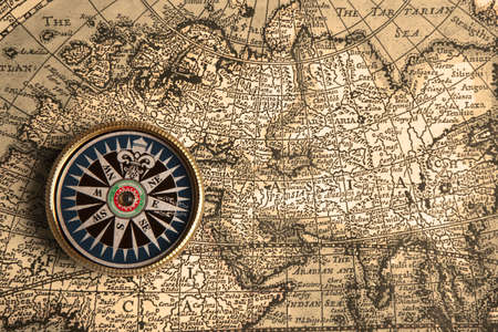 bygone: Old compass and rope on vintage map
