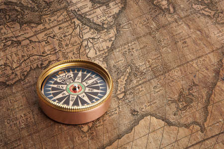 Old compass and rope on vintage map photo