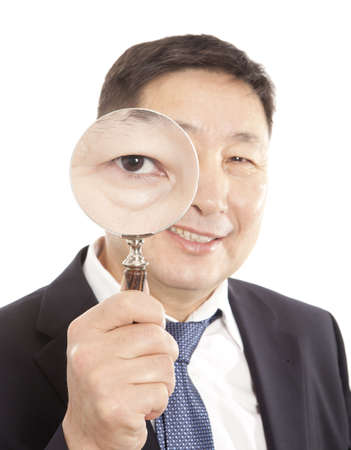 Asian businessman in a suit looking through a magnifying glass. Isolated on white background Stock Photo - 17542298