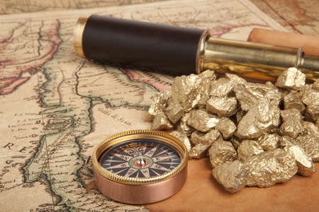 Gold nuggets and vintage brass telescope on antique map photo