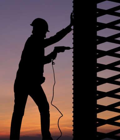 andamios: Silueta de trabajador de la construcción en contra de cielo del atardecer