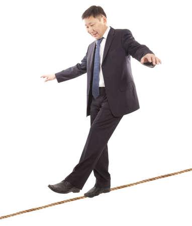 Aziatische zakenman rope-walker. Geïsoleerd op witte achtergrond