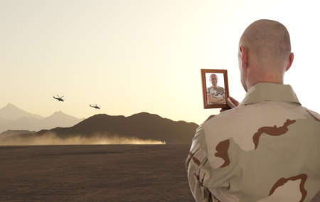 iraq war: A soldier looks at the picture of the deceased friend