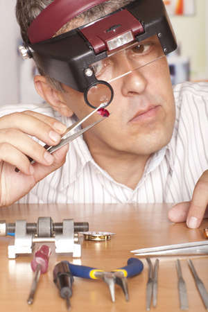 inspect: Male jeweler looking through a magnifier to check for flaws in a ruby.  Focus on ruby