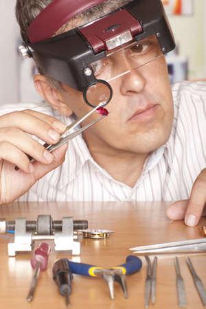 Man juwelier kijken door een vergrootglas om te controleren op gebreken in een robijn. Focus op ruby