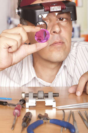 flaws: Male jeweler looking through a magnifier to check for flaws in a sapphire.  Focus on sapphire Stock Photo
