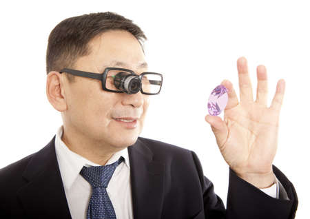 inspecting: Male jeweler looking through a magnifier to check for flaws in a sapphire