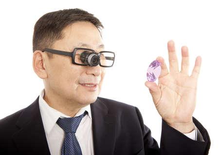 Man juwelier kijken door een vergrootglas om te controleren op gebreken in een saffier